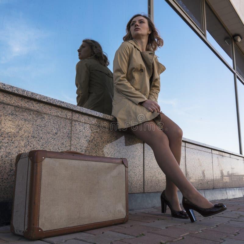 沟槽的走在带着葡萄酒手提箱的城市的可爱的年轻白肤金发的妇女画象  免版税图库摄影