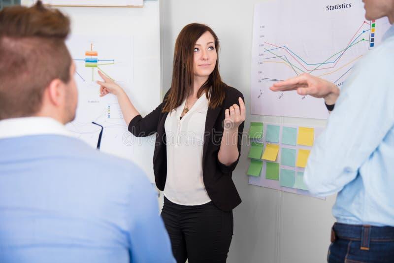 沟通与同事的女实业家,当指向查家时 库存图片