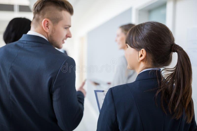 沟通与同事的女实业家,当走在办公室时 库存照片