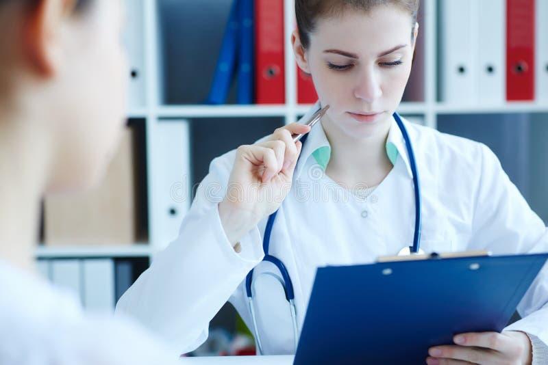 沟通与女性患者和填装的医疗形式的年轻美丽的女性医学医生 医疗保健或 免版税图库摄影
