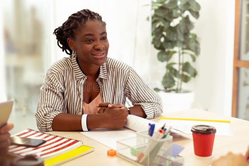 沟通与她的同学的快乐的深色皮肤的女性 库存照片