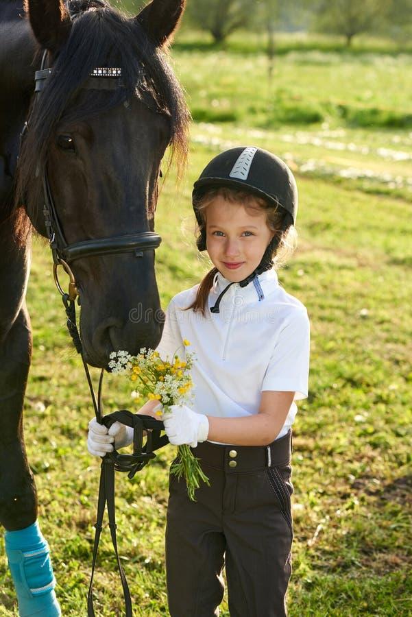 沟通与她的在专业成套装备的马的小女孩骑师 免版税库存照片