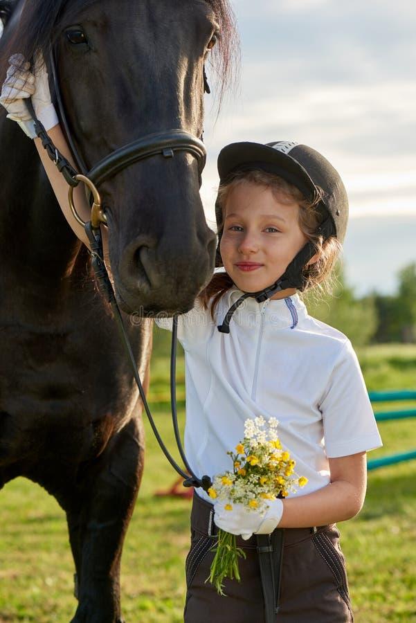 沟通与她的在专业成套装备的马的小女孩骑师 库存照片