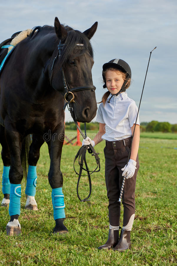沟通与她的在专业成套装备的黑马的小女孩骑师 库存图片