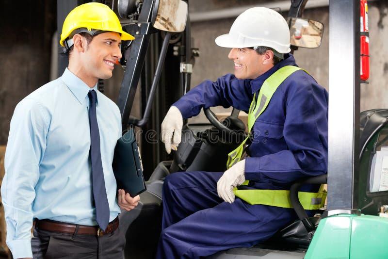 沟通与监督员的铲车司机 免版税库存图片