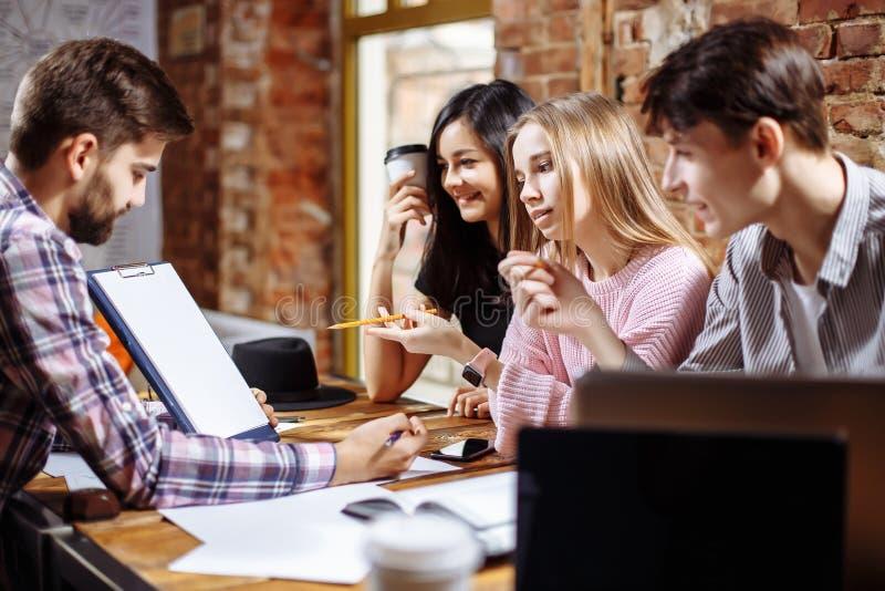 沟通在咖啡馆的学生在教训以后 免版税库存照片