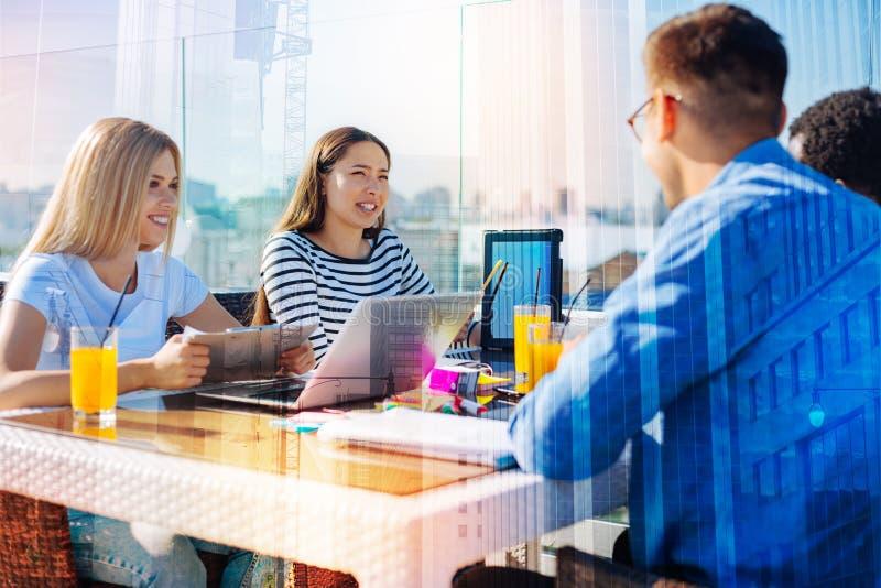 沟通在咖啡馆的高兴学生 图库摄影