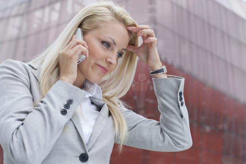 沟通在手机的迷茫的女实业家特写镜头反对办公楼 免版税库存照片