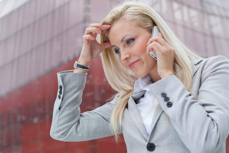 沟通在手机的迷茫的女实业家特写镜头反对办公楼 库存照片