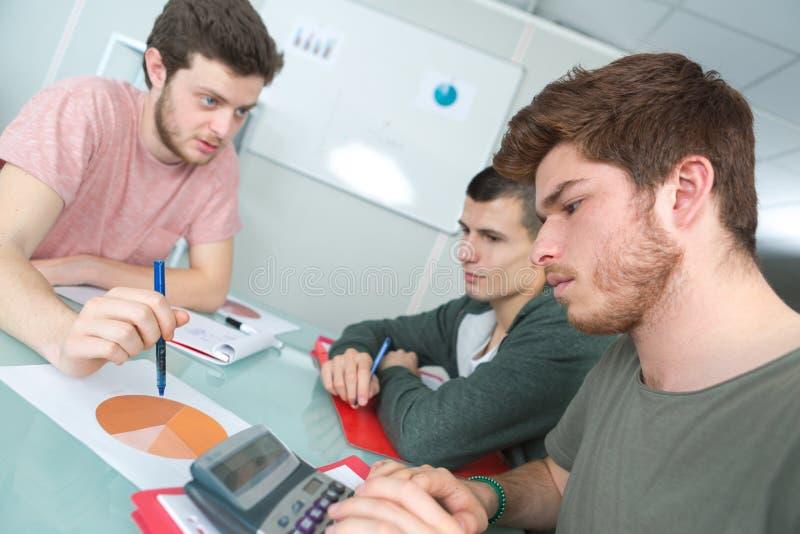 沟通在教室的三名学生 免版税图库摄影