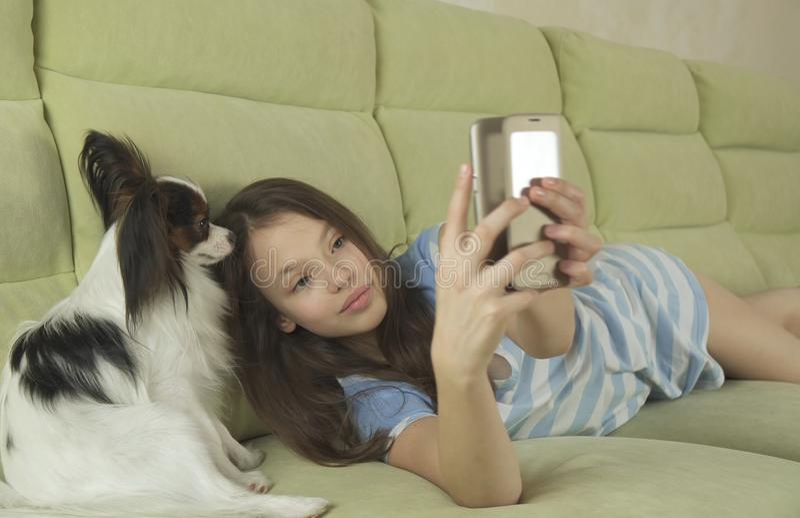 沟通在智能手机和与她的狗的美丽的愉快的十几岁的女孩 库存图片