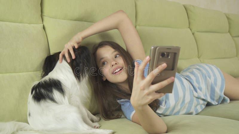 沟通在智能手机和与她的狗的美丽的愉快的十几岁的女孩 免版税库存图片