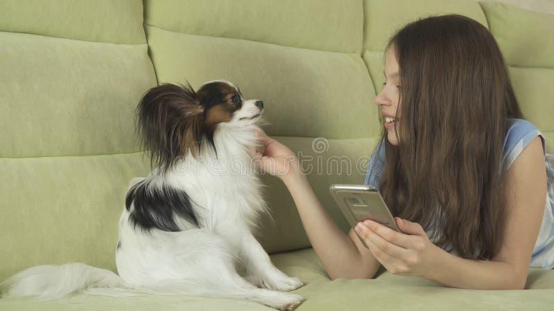 沟通在智能手机和与她的狗的美丽的愉快的十几岁的女孩 免版税库存照片