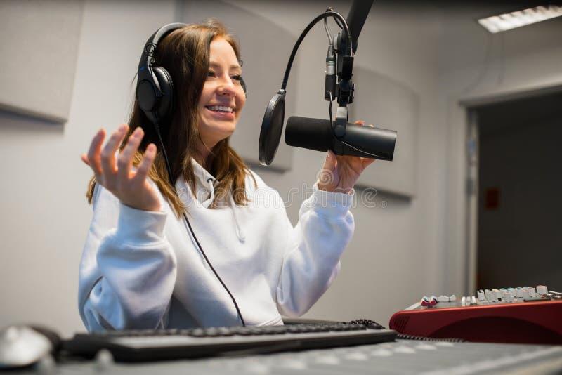 沟通在话筒的女性骑师在无线电演播室 图库摄影