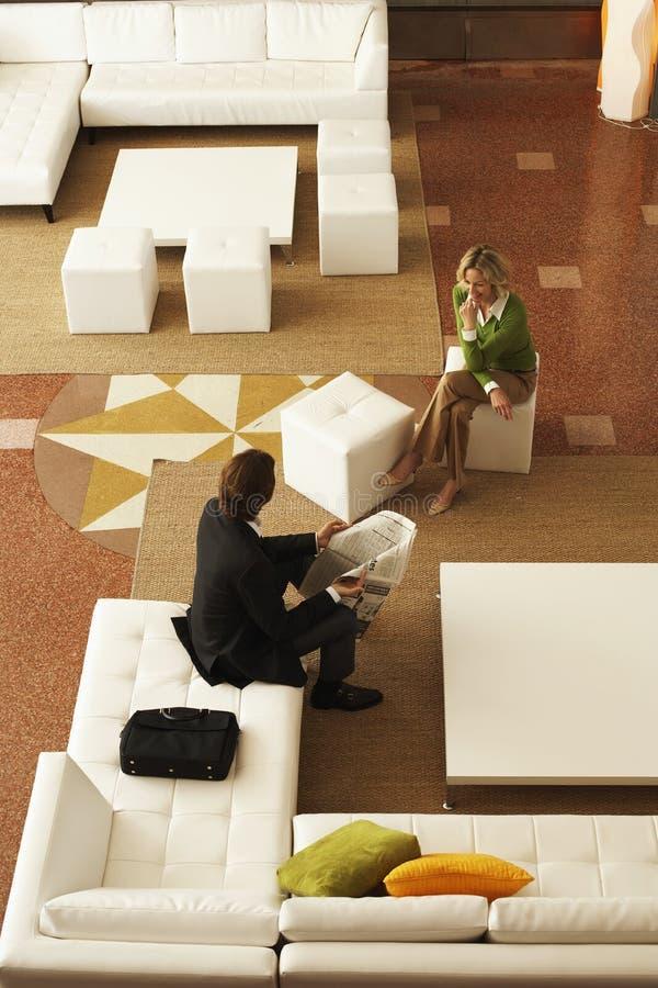 沟通的买卖人,当坐在办公室大厅时 库存图片
