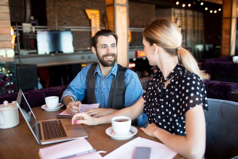 沟通的时髦的工友在自助食堂 免版税图库摄影