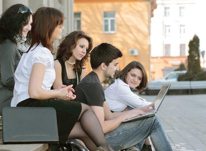 沟通通过互联网的小组学生使用膝上型计算机 图库摄影