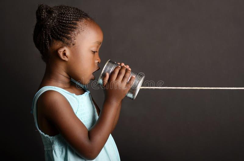 沟通通过罐子的非洲女孩 免版税库存照片