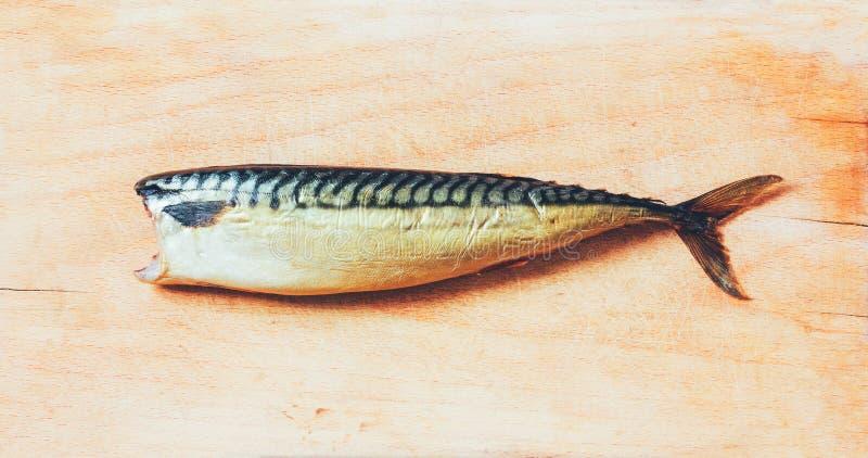 没有一个头的熏制的鲭鱼在一个木切板 免版税库存照片