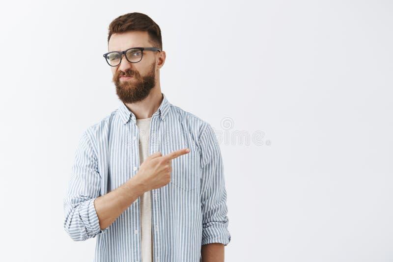 没有不如此认为 生气的和无印记的英俊的年轻男性企业家画象有长的胡子的在透明 免版税库存照片