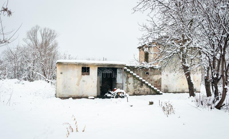 没有作为流浪者避身处和屋顶的老被放弃的废墟房子使用的窗口在空的夏天期间在与锡的寒冷冬天天 库存照片