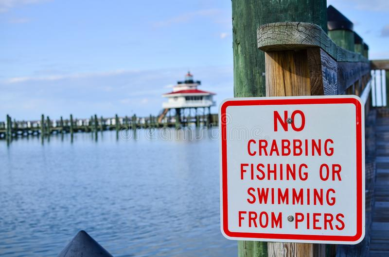没有侧航、没有钓鱼和没有游泳的标志从码头 Choptank河灯塔在马里兰在背景中弄脏了 免版税图库摄影