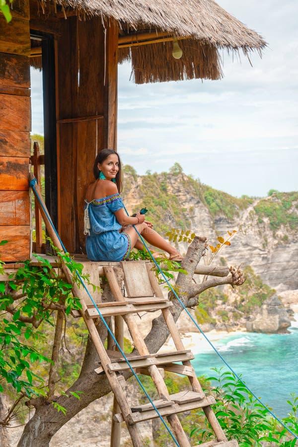 没有关心和没有仓促 放松的游泳衣的美丽的年轻女人,当坐在树上小屋里户外时 库存照片