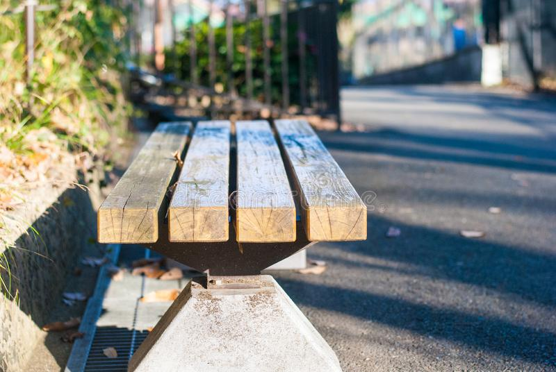 没有坐的人的长木凳在阳光感觉等待的片刻下 图库摄影