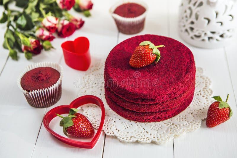 没有奶油色`红色天鹅绒`的红色蛋糕在一张白色木桌上,装饰用草莓、玫瑰和白色透雕细工花瓶有hea的 库存照片