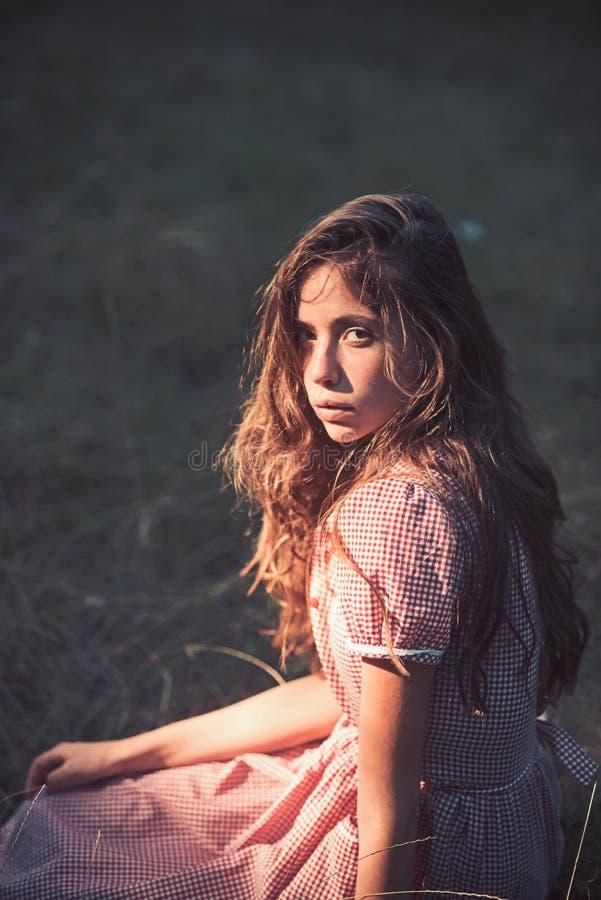 没有构成的妇女放松在葡萄酒样式的草 有长的深色的头发的秀丽女孩 在减速火箭的礼服的时装模特儿 库存图片