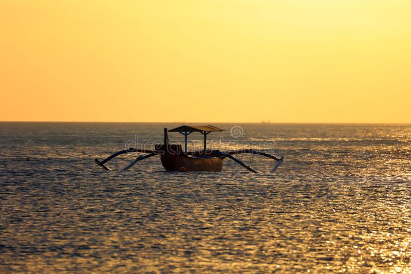 没有渔夫的渔夫小船巴厘岛的,在日落期间的印度尼西亚在海滩 图库摄影