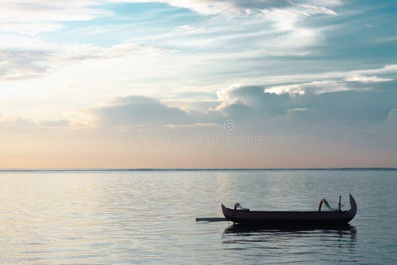 没有漂浮在非常镇静和平安的海洋的乘客的传统巴厘岛渔船 库存照片