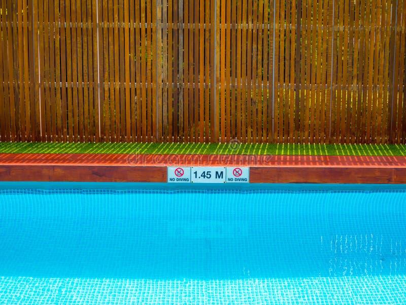 没有潜水的标志和水池深度标志在水池边缘在室外游泳场木篱芭背景的 免版税库存图片
