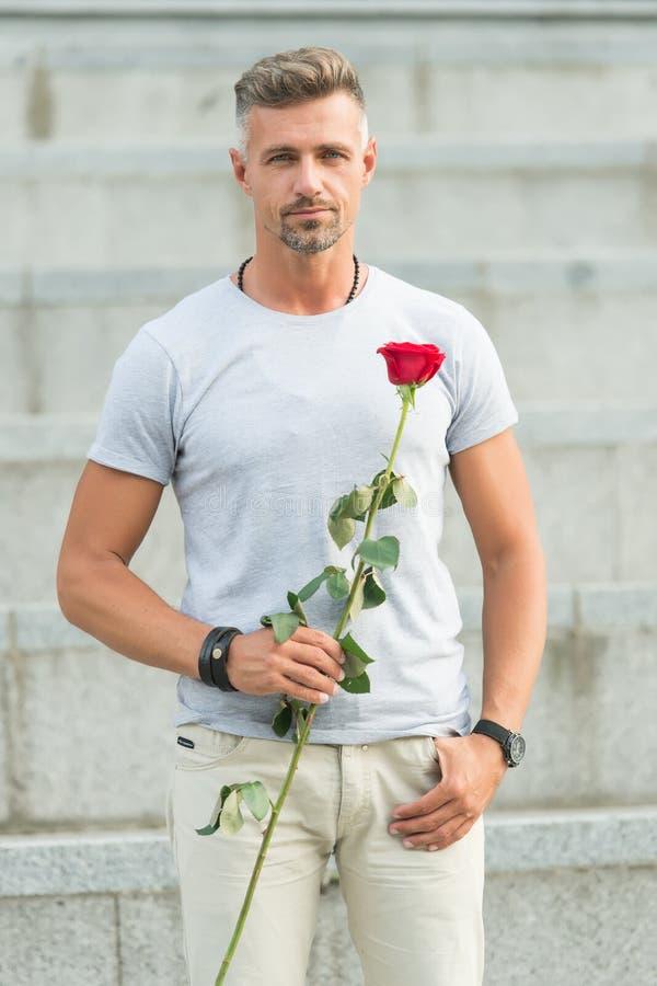 没有爱,生活太短的以至于不能居住 人成熟穿着考究的强壮男子等待他的亲爱的 有玫瑰的帅哥 免版税库存图片