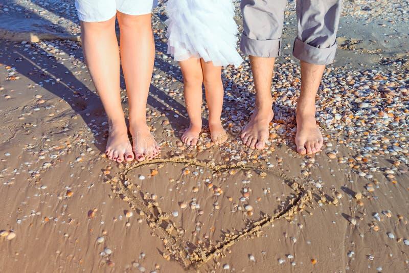 没有站立在湿沙滩的拉长的心脏形状附近的面孔三口之家在阳光下 愉快的家庭度假,旅行概念 Sel 免版税库存图片