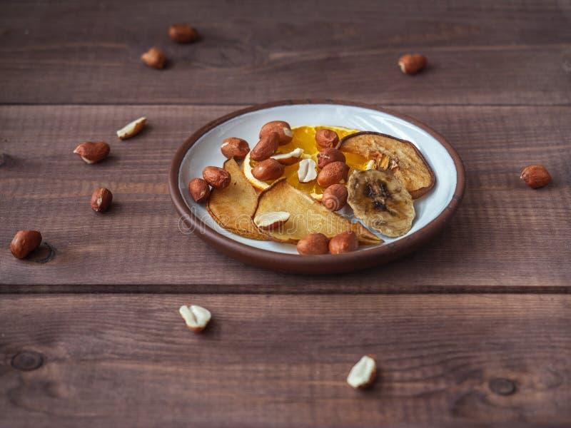 没有糖和添加剂的果子芯片在一顿健康快餐的一块小板材带领一种健康生活方式的人的 免版税库存照片