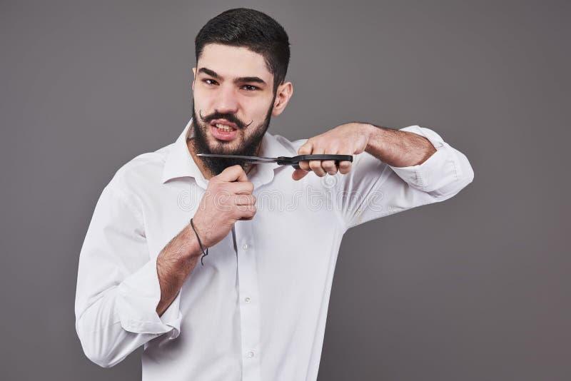 没有胡子 切开他的与剪刀的胡子和看照相机的英俊的年轻人画象,当站立时 库存图片