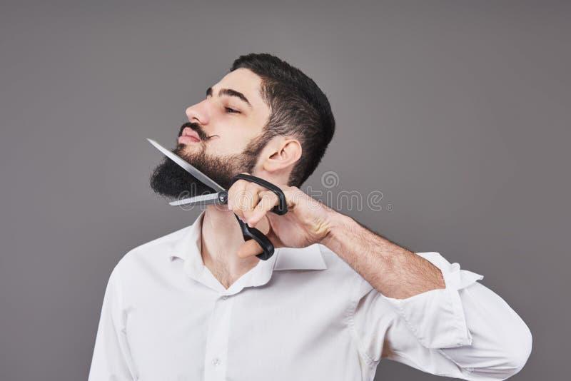 没有胡子 切开他的与剪刀的胡子和看照相机的英俊的年轻人画象,当站立时 免版税图库摄影