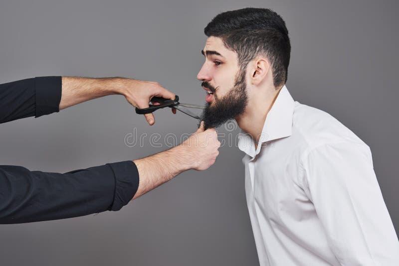 没有胡子 切开他的与剪刀的胡子和看照相机的英俊的年轻人画象,当站立时 免版税库存图片