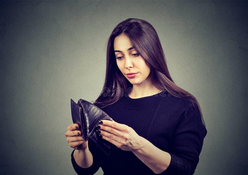 没有金钱的妇女 拿着空的钱包的哀伤的女商人 免版税库存照片