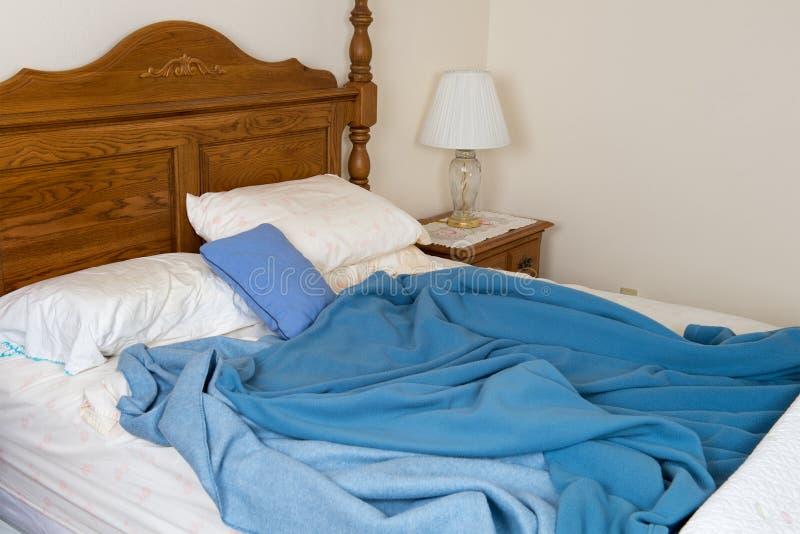 没有整理好的杂乱床,家庭卧室 免版税库存图片