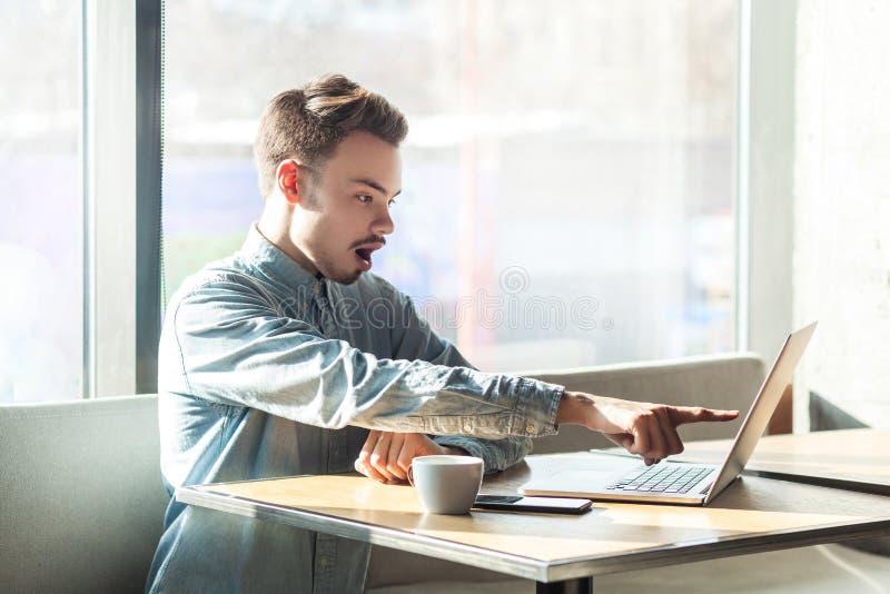 没门!惊人的蓝色衬衣的翻倒有胡子的年轻上司侧视图画象在咖啡馆坐,运作并且打视频通话  库存图片