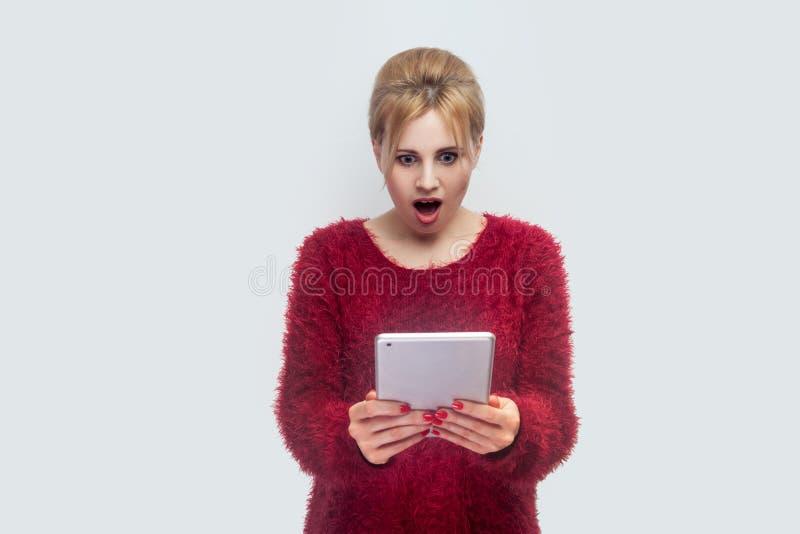 没门!美丽的难以相信的年轻女人画象站立和观看在她的片剂的红色女衬衫的惊奇的录影与 库存照片