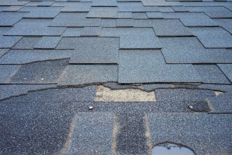 沥清木瓦需要修理的屋顶损伤接近的看法  免版税库存照片
