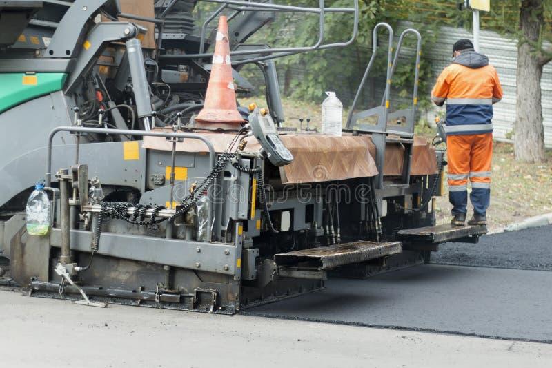 沥青摊铺机机器或摊铺机修整机地方每新鲜的热的沥青层数  库存图片