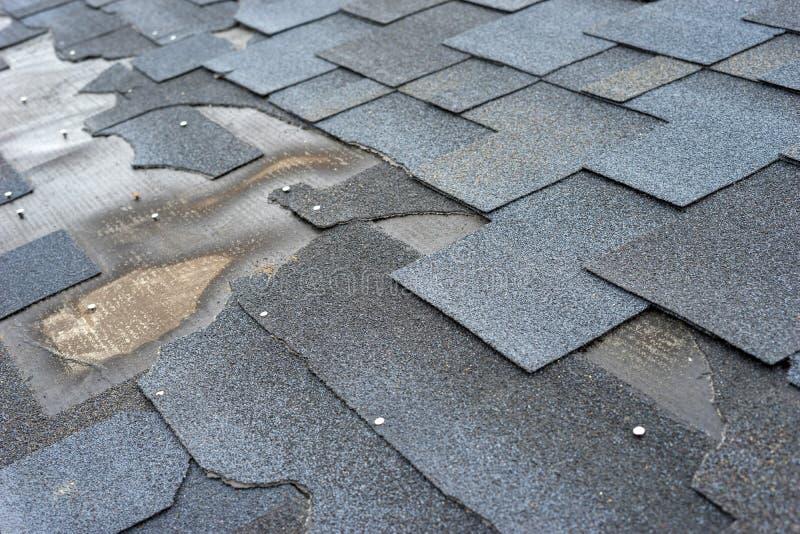 沥青木瓦需要修理的屋顶损伤看法的Сlose  库存图片