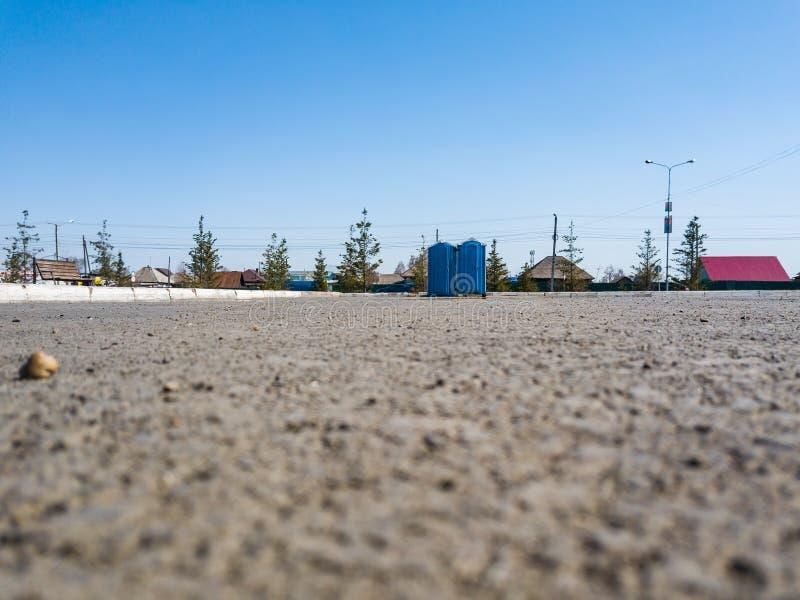 沥青的底部在两蓝色干燥壁橱的在公园在男人和妇女的假日前没有在蓝色明白下的人 图库摄影