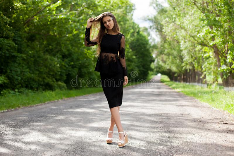 沥青老路的陡峭的苗条乌克兰妇女 库存图片