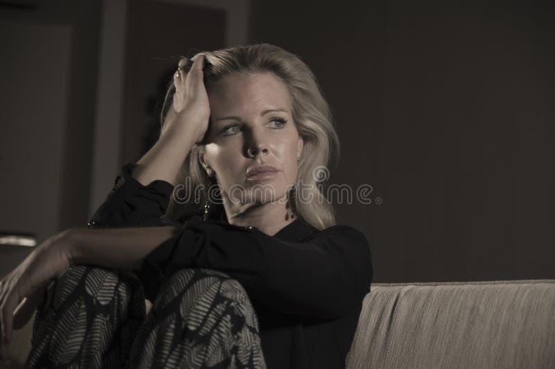 沮丧和急切美丽的白肤金发的在家感觉被挫败的开会沙发长沙发哀伤和d的妇女遭受的消沉和痛苦 免版税库存照片