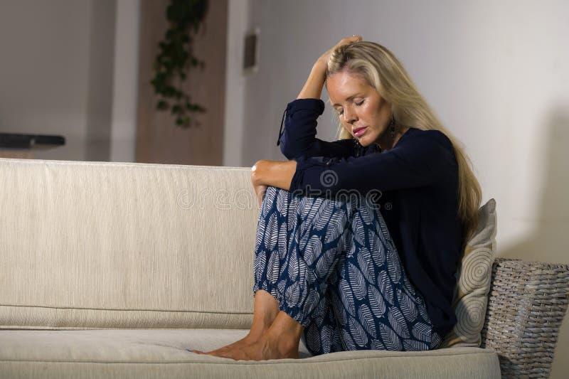 沮丧和急切美丽的白肤金发的妇女遭受的消沉和忧虑危机感觉被挫败的和认为偏僻在hom 免版税库存照片